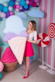 大きなアイスクリームを保持しているピンクのドレスの若い女性の肖像画