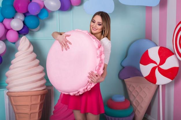 大きなマカロンを保持しているピンクのドレスの若い女性の肖像画