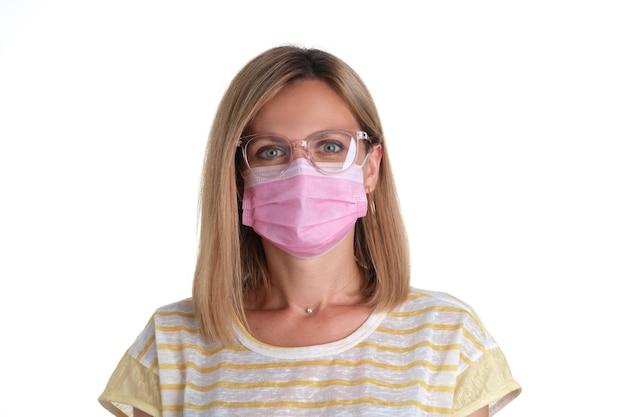 분홍색 보호 의료 마스크와 시력을 위한 안경을 쓴 젊은 여성의 초상화. covid 19 감염 개념의 예방