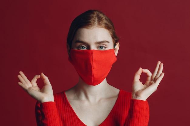 붉은 벽 요가 진정 선과 명상 covid pandemia 개념에 고립 보호 의료 얼굴 마스크에 젊은 여자의 초상화