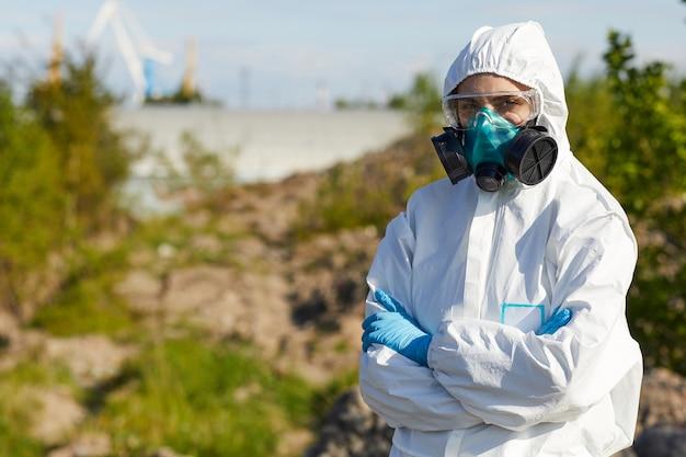 腕を組んで立っている保護作業服とマスクの若い女性の肖像画。彼女は危険な地域で働いています