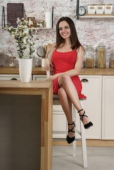 Портрет молодой женщины в красном платье, сидя на кухне