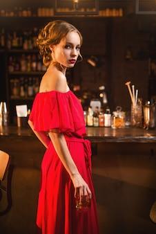 バーのカウンターに立っている赤いドレスの若い女性の肖像画。クラブで手に飲み物を持つ美しい女性