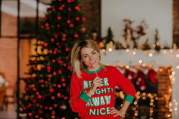 Портрет молодой женщины в красной пижаме санты представляя с свечой рождества против красных светов рождественской елки.