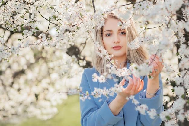 Портрет молодой женщины в цветущем саду в весеннее время. цветущие цветы миндаля