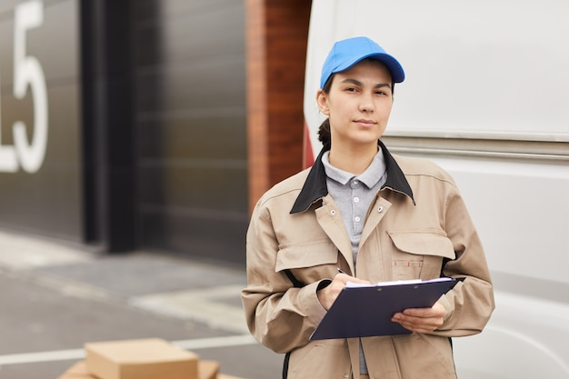 Портрет молодой женщины в форме, заполняющей форму, стоя на открытом воздухе, она работает на складе доставки