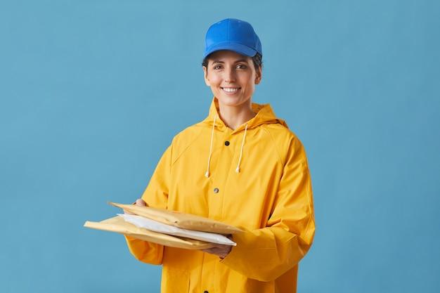 Портрет молодой женщины в форме, держащей посылки в руках и улыбающейся изолированной на синем