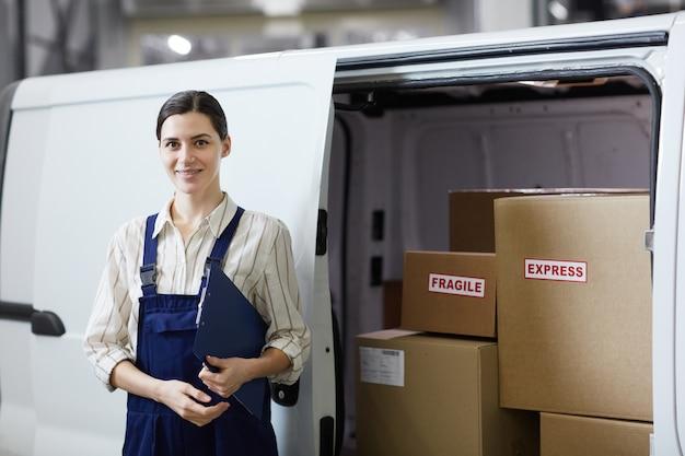 Портрет молодой женщины в униформе, улыбаясь в камеру, стоящую возле грузовика, работающего в службе доставки