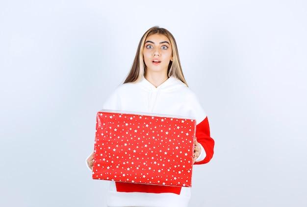 Портрет молодой женщины в теплой толстовке с капюшоном, держащей рождественский подарок