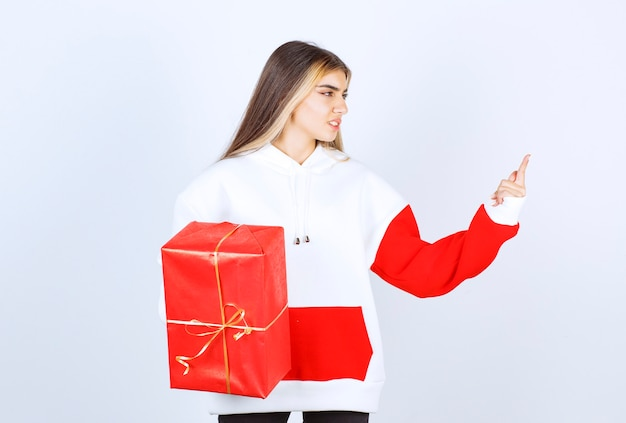 크리스마스 선물을 들고 따뜻한 스웨터에 젊은 여자의 초상화