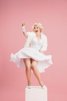 伝説的な女優としてのコーラルピンクの壁の女性モデルの白いドレスを着た若い女性の肖像画は、時代の比較の概念をピンで留めます現代のファッションの美しさ