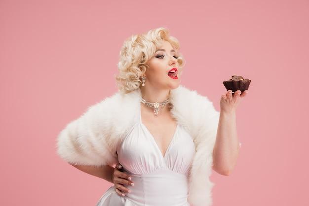 Портрет молодой женщины в белом платье на кораллово-розовой стене женской модели в образе легендарной актрисы подкалывать концепцию сравнения эпох современной модной красоты