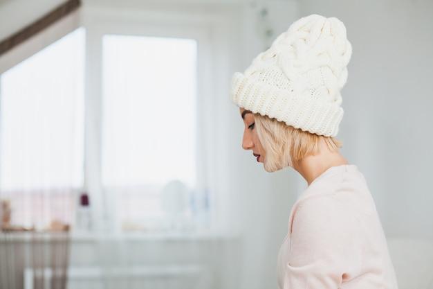 흰 손 니트 모자에 젊은 여자의 초상화