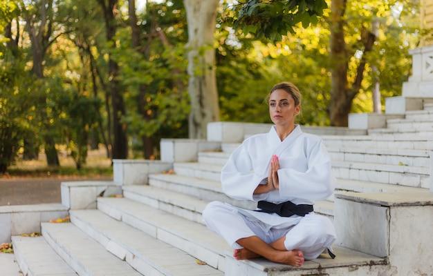 Портрет молодой женщины в белом кимоно с черным поясом. спортивная женщина, сидящая на лестнице и размышляющая на открытом воздухе. боевые искусства