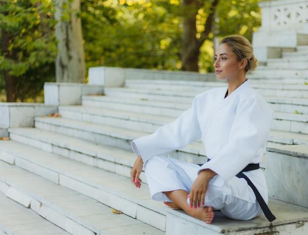 Портрет молодой женщины в белом кимоно с черным поясом. спортивная женщина сидит на лестнице на открытом воздухе. боевые искусства