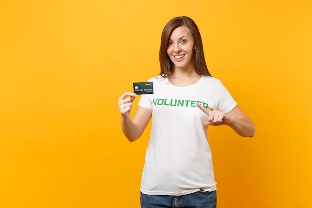書かれた碑文の緑のタイトルのボランティアが黄色の背景で隔離のクレジット銀行カードを保持している白いtシャツの若い女性の肖像画。自主的な無料支援支援、チャリティーグレイスワークコンセプト。