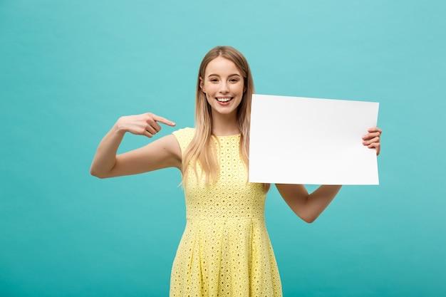 側面の白い空白のボードに指を指す黄色のドレスの若い女性の肖像画。青い背景の上に分離。