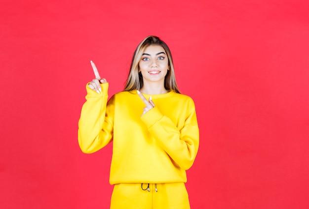 Портрет молодой женщины в желтом наряде, указывая куда-то