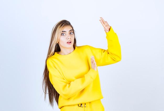Портрет молодой женщины в желтом наряде позирует и стоя
