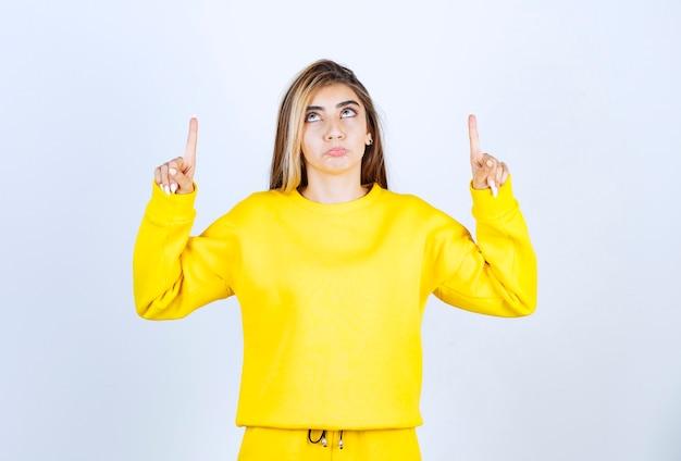 카메라에 포즈를 취하는 노란색 옷을 입은 젊은 여성의 초상화