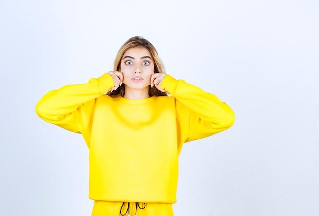 흰 벽 위에 서서 포즈를 취하는 노란 옷을 입은 젊은 여성의 초상화