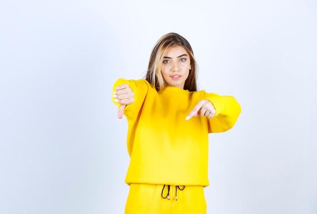 노란색 옷을 입고 긍정적인 자세로 서 있는 젊은 여성의 초상화