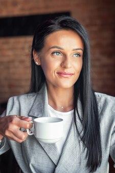 Портрет молодой женщины держит чашку кофе, улыбаясь в кафе кафе.