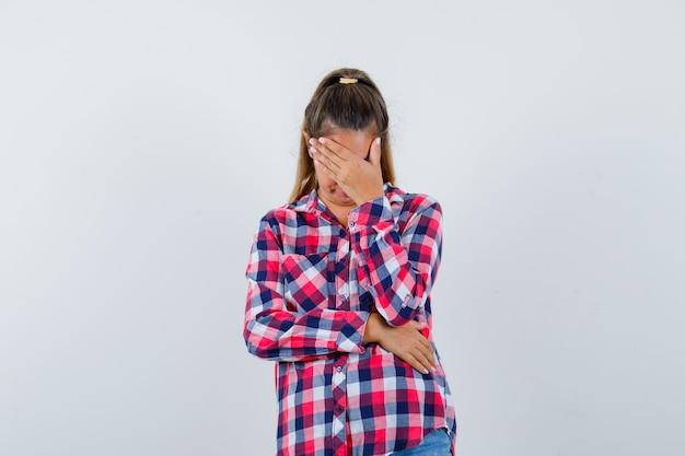 캐주얼 셔츠에 얼굴에 손을 유지하고 우울한 전면보기를 찾고 젊은 여자의 초상화