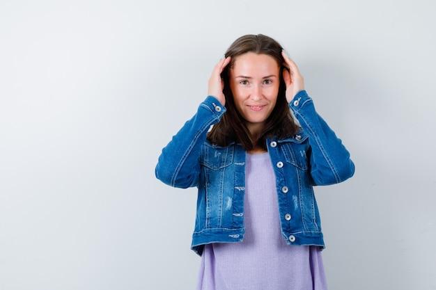 Портрет молодой женщины, держащей руки на голове в футболке, куртке и выглядящей стыдно, вид спереди