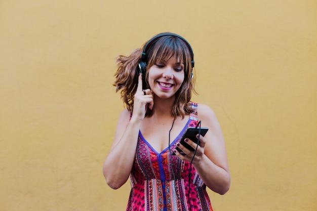 Портрет молодой женщины, слушать музыку на гарнитуру и мобильный телефон