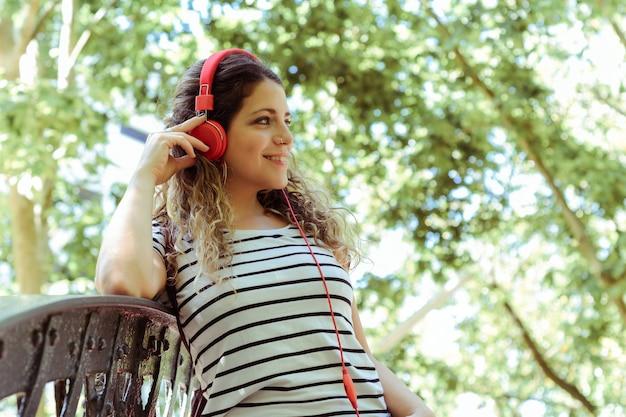 거리에서 파란색 헤드폰으로 음악을 듣고 젊은 여자의 초상화. 옥외.