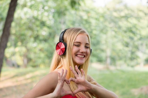 헤드폰으로 음악을 듣고 공원에서 웃는 젊은 여성의 초상화.