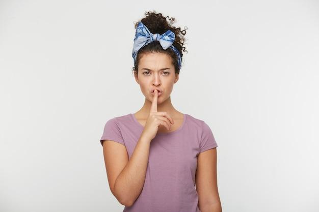 若い女性の肖像画は厳格に見える、彼女の口に彼女の指を保持します