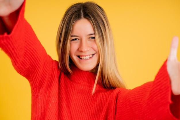カメラを見て、スタジオで自分撮りをしながら笑っている若い女性の肖像画。