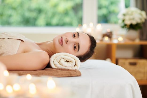 스파 살롱에서 침대에서 쉬면서 카메라를 보고 있는 젊은 여성의 초상화