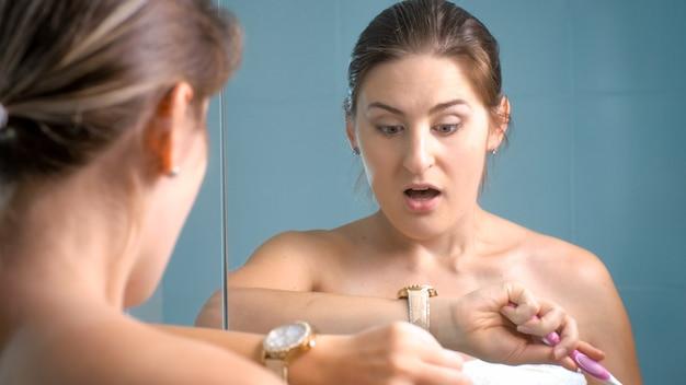 腕時計を見て、朝仕事に遅れている若い女性の肖像画。