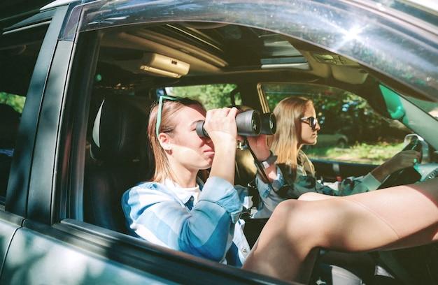 彼女の友人がロードトリップの冒険で運転している間双眼鏡を通して見ている若い女性の肖像画。女性の友情と余暇の概念。