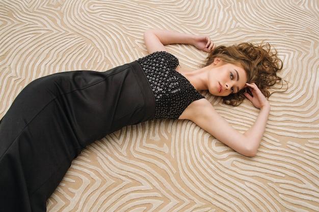 イブニングドレスのカーペットの上に横たわっている若い女性の肖像画
