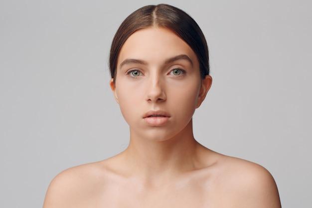 Портрет молодой женщины модели в студии с естественным макияжем. концепция макияжа.