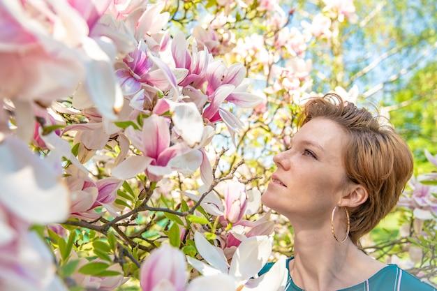 Портрет молодой женщины возле цветущей магнолии
