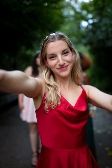 Портрет молодой женщины рядом со своими друзьями на выпускном вечере
