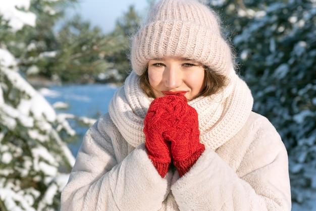 Портрет молодой женщины на открытом воздухе зимой. вязаная шапка и варежки.