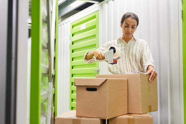자기 저장 장치, 복사 공간에 의해 서있는 동안 테이프 총으로 상자를 포장하는 젊은 여자의 초상화