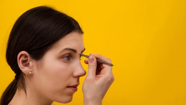 Портрет молодой женщины, выщипывая брови пинцетом на желтом фоне.