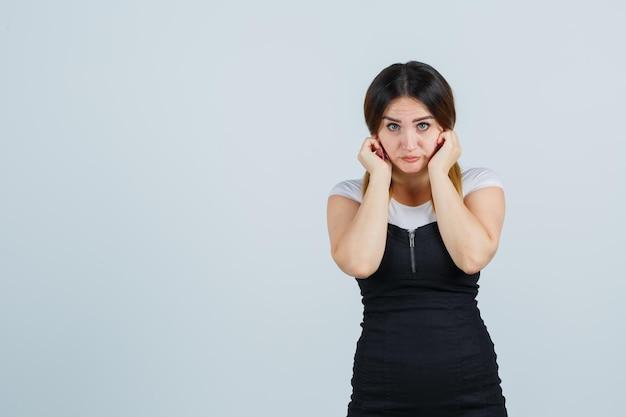 指で耳を塞ぎ、怖がって見える若い女性の肖像画