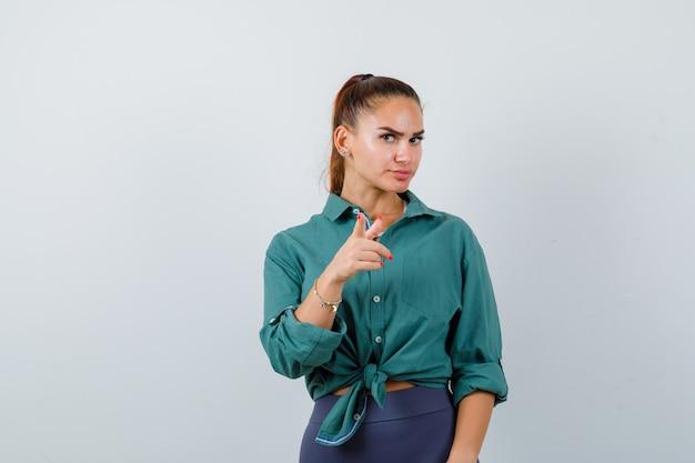 緑のシャツでカメラを指して、真剣な正面図を見て若い女性の肖像画