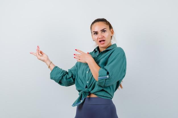 Портрет молодой женщины, указывающей влево в зеленой рубашке и смотрящей с удивлением, вид спереди