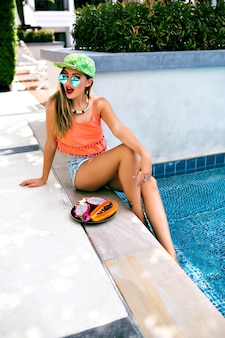 Портрет молодой женщины, позирующей возле бассейна с тропическими фруктами
