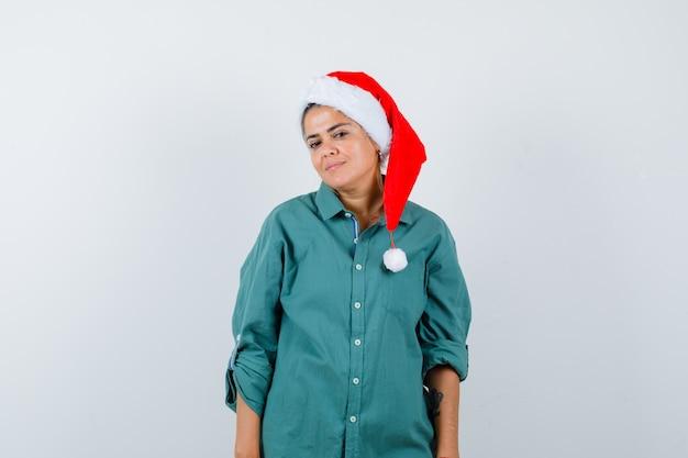 Портрет молодой женщины, позирующей, стоя в рубашке, шляпе санты и уверенно выглядящей, вид спереди