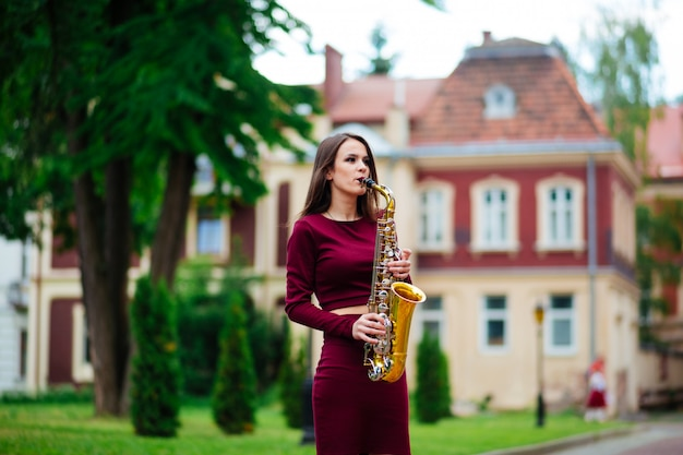 Портрет молодой женщины, позируя с саксофоном в парке